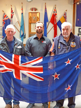 Waiheke RSA president Campbell Farquhar, war veteran Rod Hinchco and RSA secretary manager Brendan Demchy hold the current flag that they support retaining.