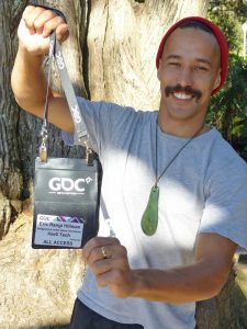 Eric Rangi Hillman holds up his pass to a recent international Game Developers Conference in San Francisco.