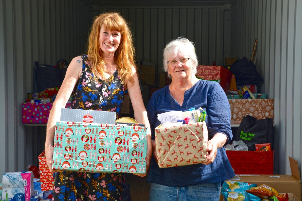 Who needs Santa? Amelia Lawley and Maggie Wikaira show off just some of the gifts that generous islanders have donated by the container-load. Photo Sophie Boladeras